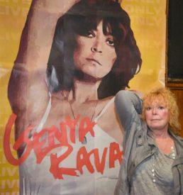 Genya Ravan poses in front of her portrait