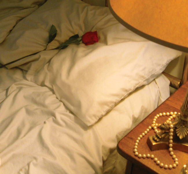 Tuesday Morning image: bed, with red rose on the pillow